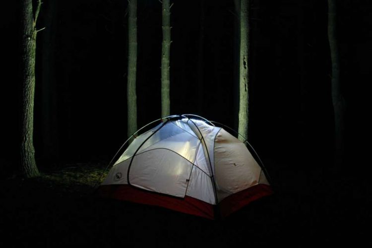 A tent with light on in the dark