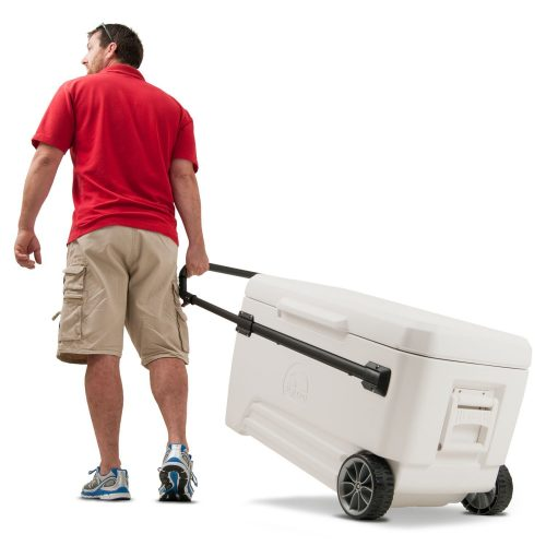 man pulling a cooler with wheels and handles