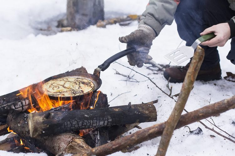 Pancakes cooking over an open camp fire in winter