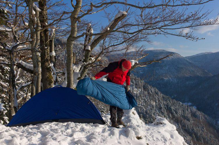 A camper preparing his sleeping bag on a snowy hill