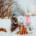 3 campers keeping warm by the camp fire