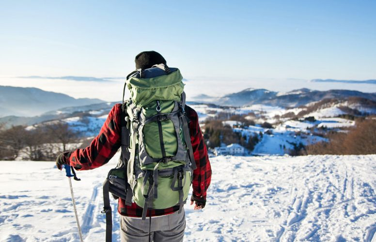 A man with backpack and cold weather hiking gear walking in the snow