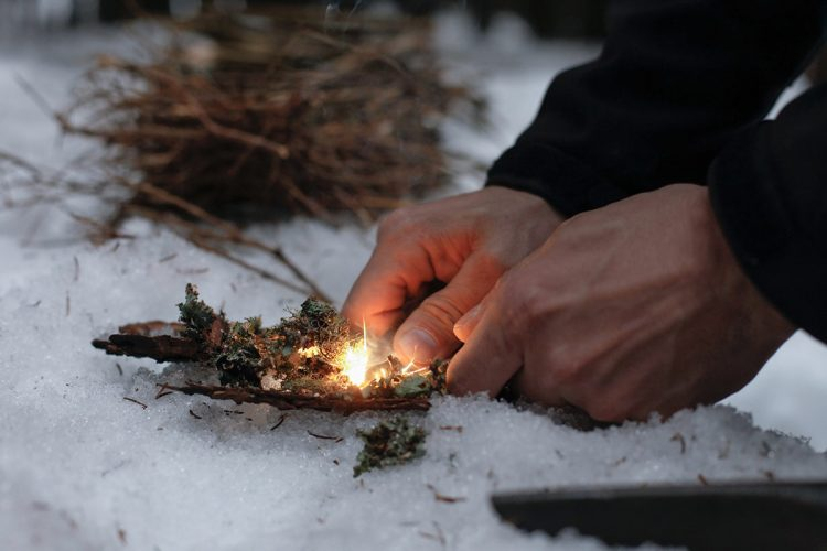 Close up of firelighting with kindling in the snow