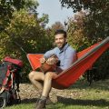 Sitting playing guitar in backpacking hammock