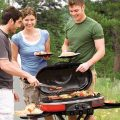 a group uses a Coleman portable camping grill