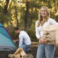 Lady carrying Dometic portable camping toilet
