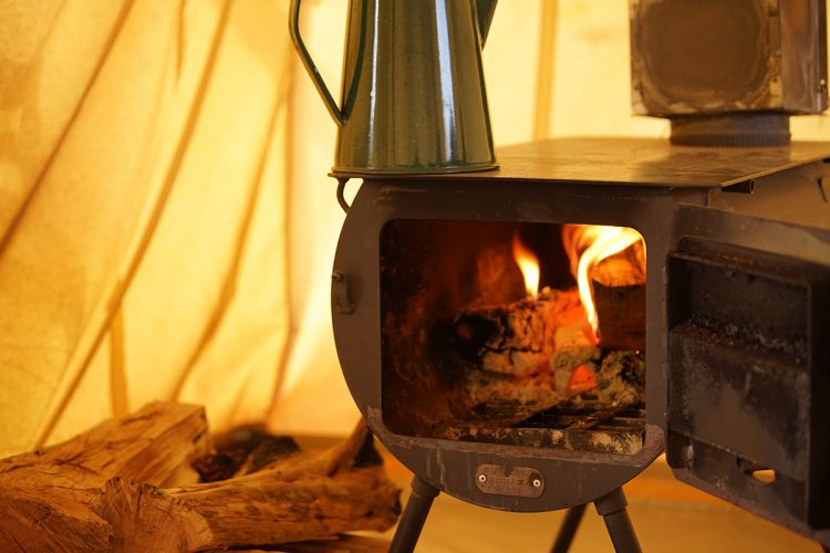 A wood burning tent stove, door open with a kettle on top
