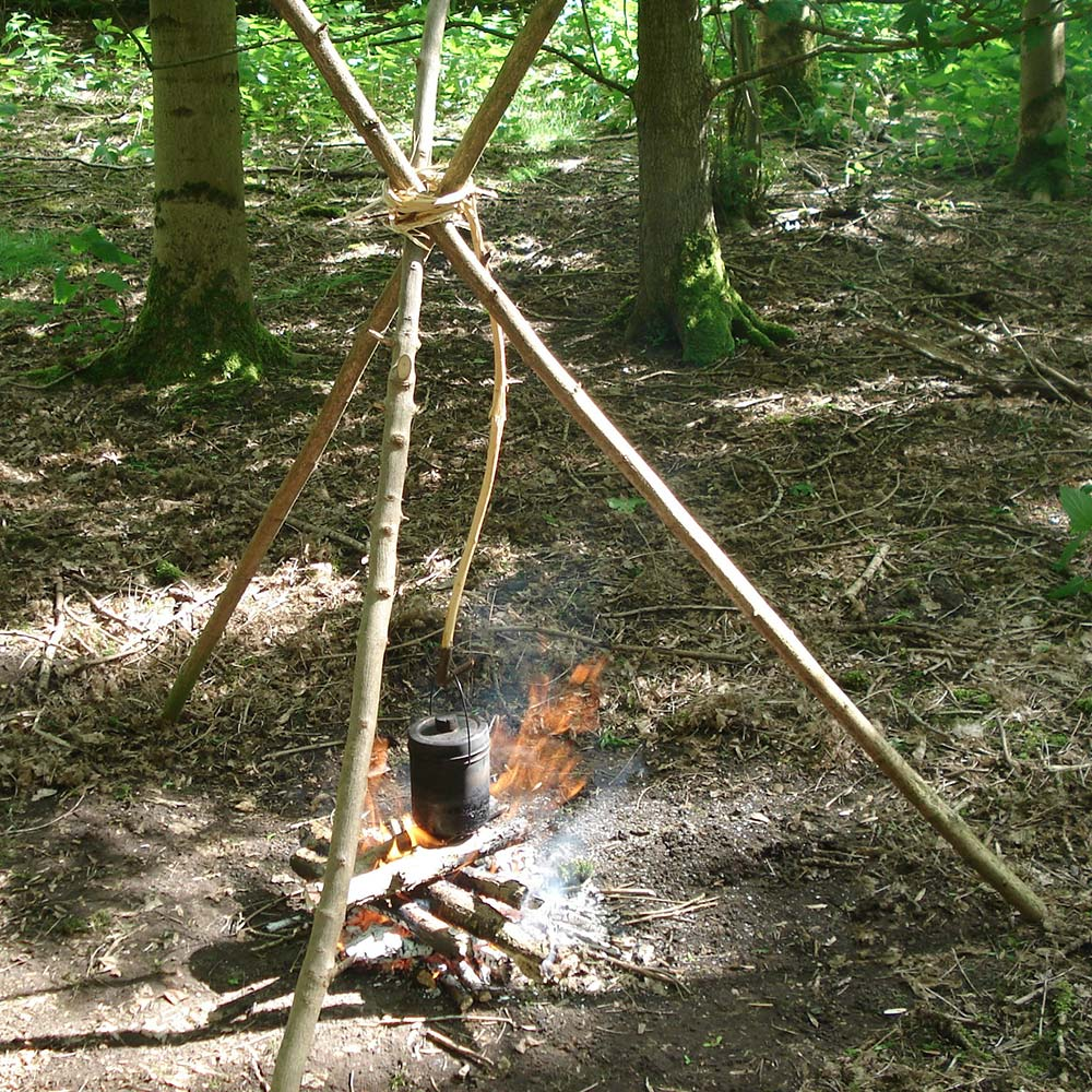 Boiling water over a camp fire using a tripod to suspend the pot