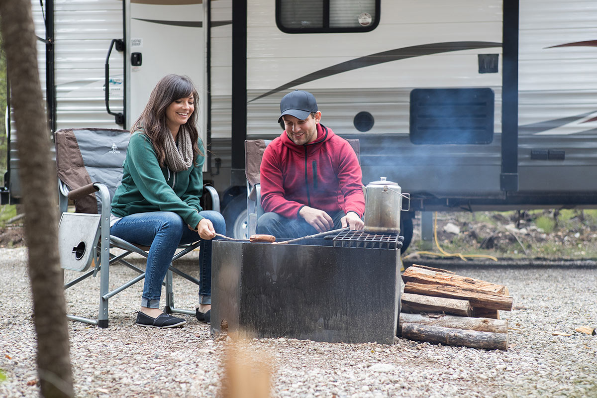 A couple cooking beside their RV while dry camping